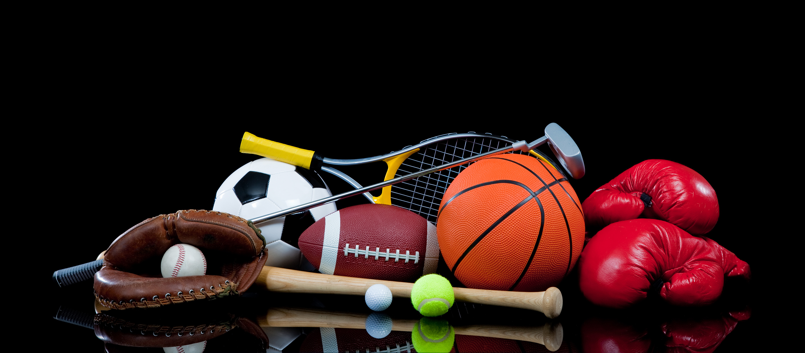 A group of sports equipment on black background including tennis, basketball, baseball, american fotball and soccer and boxing equipment