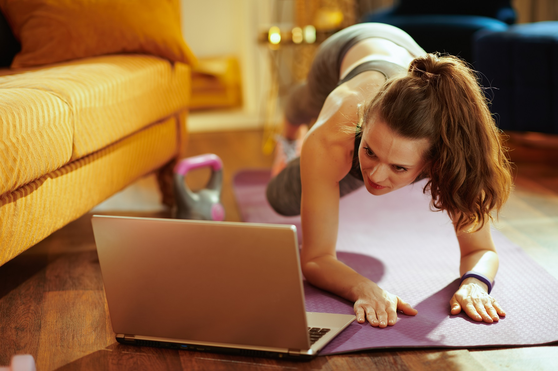 fit woman in fitness clothes in the modern house using online personal fitness trainer service in laptop and doing cardio exercises on fitness mat.