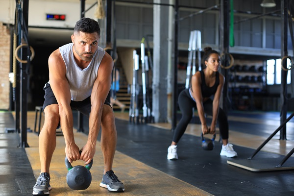 Fit and muscular couple focused on lifting a dumbbell during an exercise class in a gym