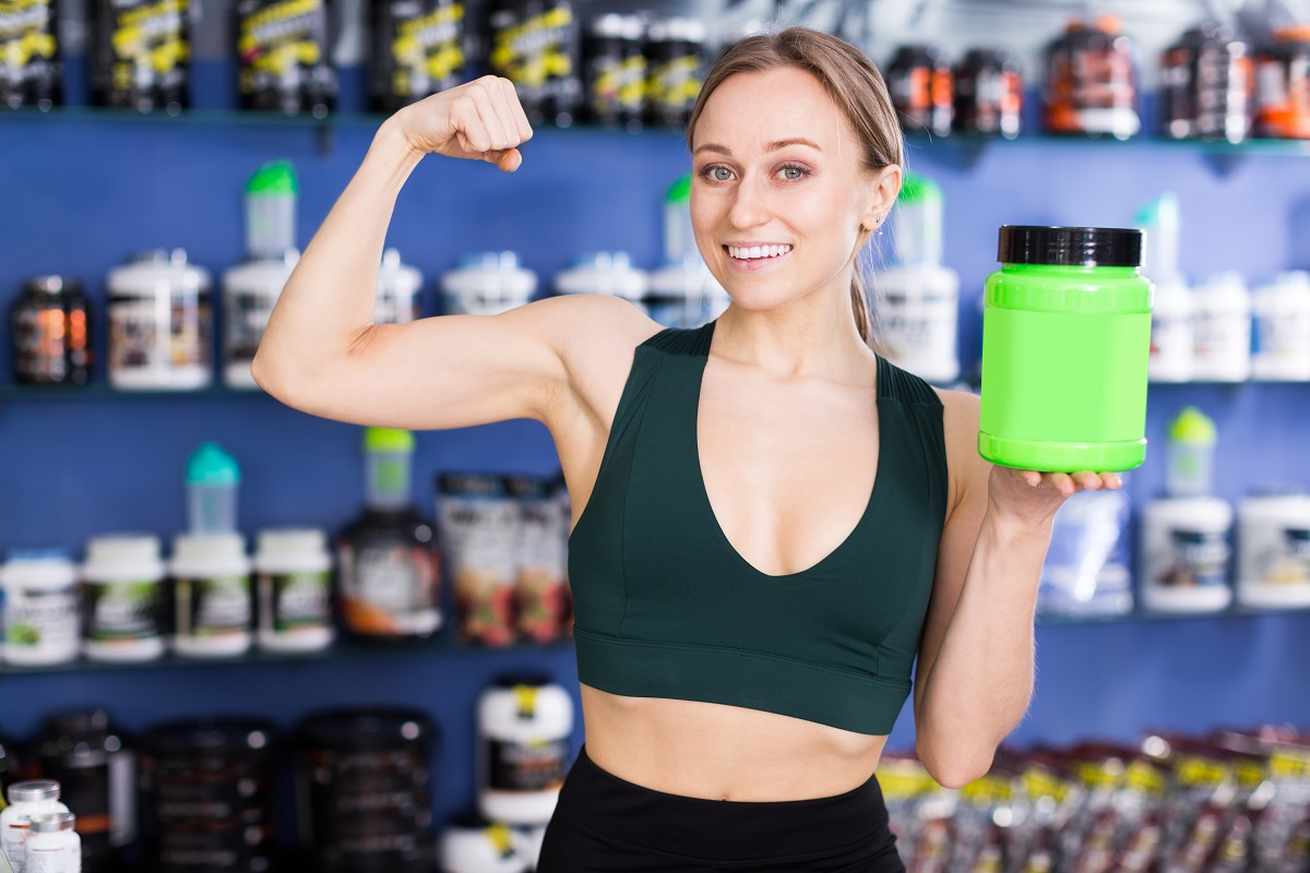 Happy fit girl demonstrating muscles while standing in store with jars of sports nutritional supplements
